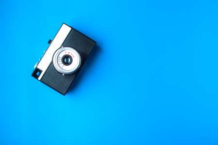Old rangefinder vintage camera on blue background