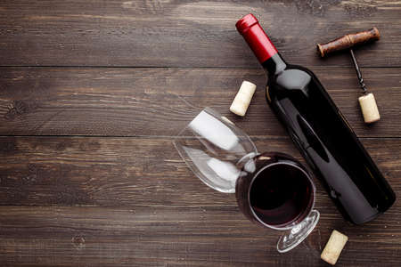 Glass bottle of wine with corks on wooden table background.Top view with copy space 스톡 콘텐츠