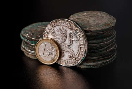The treasure of thalers and Roman denarii along with modern European coins. The concept of business. Imagens