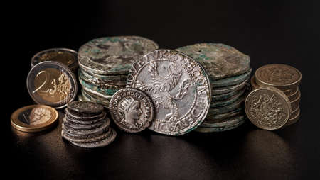 The treasure of thalers and Roman denarii along with modern European coins. The concept of business.