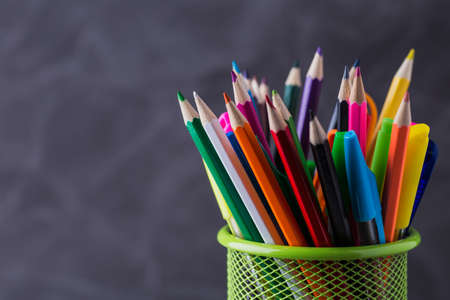 Pens and pencils in metal holder in front of wall background Stok Fotoğraf