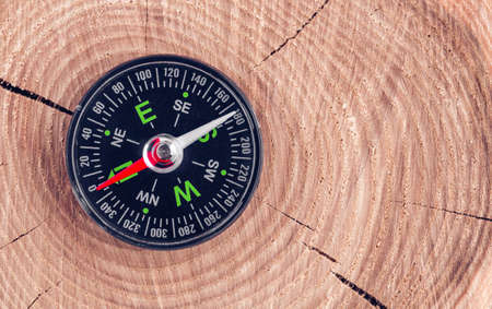 compass on wood background concept for direction, travel, guidance or assistance