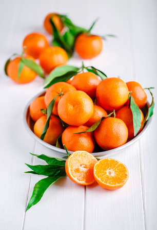 Tangerines (oranges, clementines, citrus fruits) with green leaves over wooden background with copy space.bowl of fresh mandarins Stock Photo