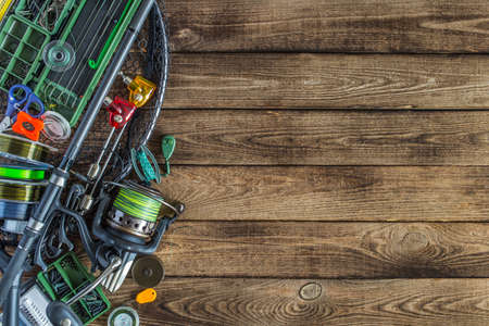 Fishing tackle - fishing spinning,Carp fishing rods, hooks and lures, fishing rod, fishing line, coil on darken wooden background