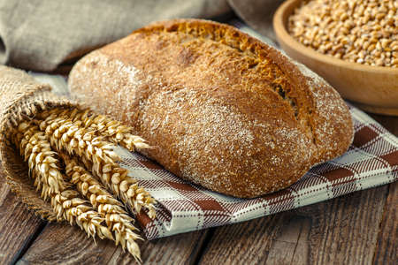 Brotlaib auf Holzuntergrund, Lebensmittelnahaufnahme. Frisches hausgemachtes Brot. Französisches Brot. Brot im Sauerteig. Ungesäuertes Brot. Ciabatta-Brot. Standard-Bild