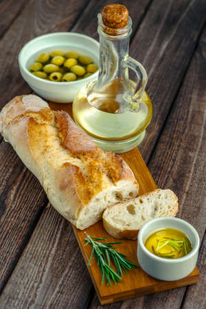 Sliced freshly baked ciabatta bread on wooden cutting board on rustic table with rosemary, salt, olives, and olive oil. Italian food concept.
