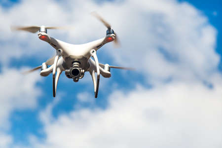 white drone hovering in a bright blue sky. New technology in the aero photo shooting.UAV drone copter flying with digital camera.Flying camera take a photo and video.