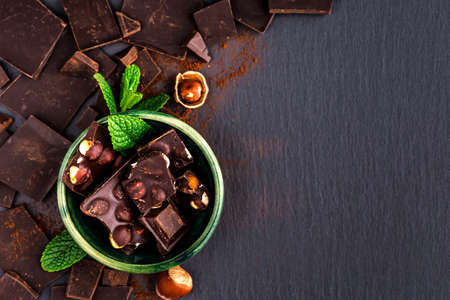 Chocolate on dark stone background. Top view with copy space