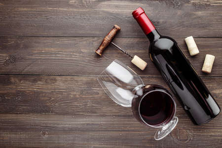 Glass bottle of wine with corks on wooden table background.Top view with copy space