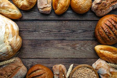 Asortyment pieczonego chleba na tle drewnianego stołu, widok z góry