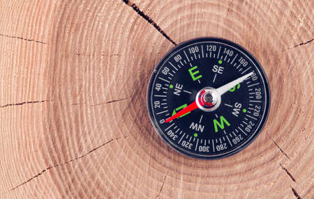 bussola su sfondo di legno concetto per direzione, viaggio, guida o assistenza