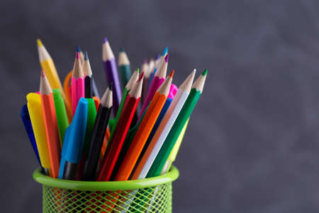 Pens and pencils in metal holder in front of wall background Stok Fotoğraf - 129481710