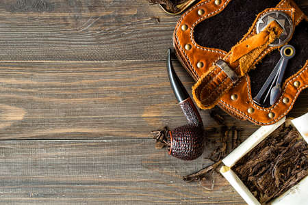 Wooden pipe with tobacco on wooden table. Tin boxes with tobacco, pipes and vintage background. Gentle man concept. Still life and prodoct photography.