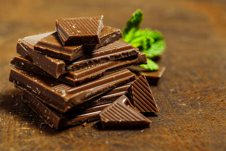 Hazelnut and almond milk and dark chocolate pieces tower.Chocolate bar pieces. Sweet food photo concept. The chunks of broken chocolate 免版税图像