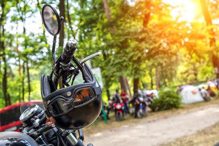 Il manubrio cromato di una moto.Viaggi e libertà, attività outdoor. Vista del manubrio della moto sullo sfondo molte moto sfocate, concetto di velocità e viaggio nella natura Archivio Fotografico