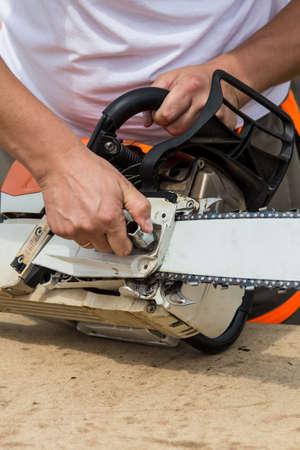 Professional technician working by repair service.Repairing chainsaw in repair shop.