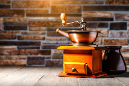 still life with coffee beans and old coffee mill on the wooden background,coffee grinder,coffee accessories brown clay cup vintage wooden mill and sack with beans scoop on old wood background