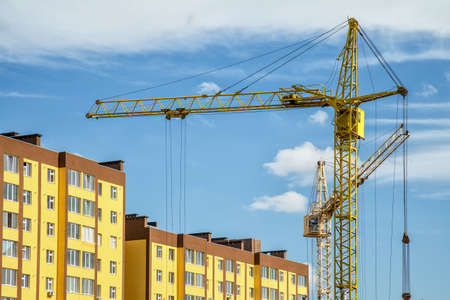 Building crane and buildings under construction against evening sky,House under construction. Industrial skyline Reklamní fotografie