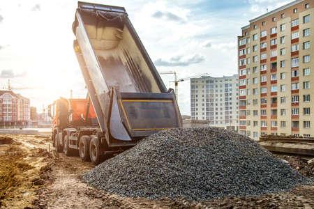 Camion de construction déversant du gravier sur un chantier de construction de routes, un camion-benne et un ripper au travail préparant le terrain pour un nouveau lotissement, processus de déchargement de camion à benne basculante, Banque d'images
