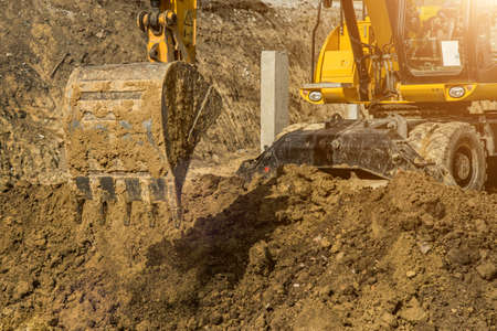 Working Excavator Tractor Digging A Trench At Construction Site.Close-up of a construction site excavator