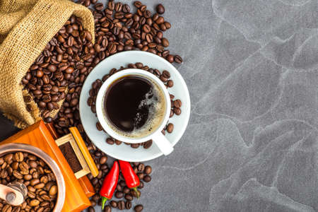 Coffee cup with roasted beans on stone background.Cup of espresso and a small Breakfast croissants, Top view with copy space for your text