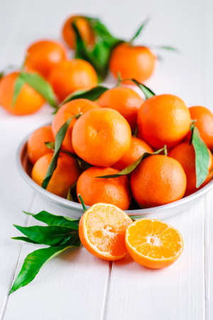 Tangerines (oranges, clementines, citrus fruits) with green leaves over wooden background with copy space.bowl of fresh mandarins Reklamní fotografie