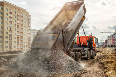 Construction truck tipping dumping gravel on road construction site,tip truck and ripper at work preparing ground for new housing estate,Dump truck unloading process, Reklamní fotografie