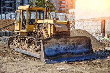 Yellow Bulldozer on new construction site, with the bright sun and nice blue sky in the background,Bulldozer working on Dirt in the Construction Site Reklamní fotografie