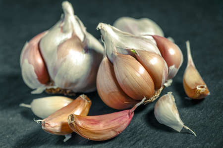 Organic garlic,Closeup garlic on wooden texture on for cooking on dark background, concept healthy lifestyle.Fresh peeled garlics and bulbs.