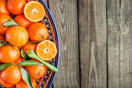 Ripe Mandarin fruit peeled open and place on old rustic look timber with group of mandarin fruits and leaves out of focus on the background Reklamní fotografie