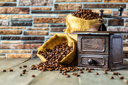 Antique vintage retro bronze coffee mill on black wooden board with roasted coffee beans,coffee accessories brown clay cup vintage wooden mill and sack with beans scoop on old wood background