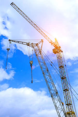 Construction site background. Hoisting cranes and new multi-storey buildings. I.ndustrial background.Building construction site work against blue sky Stok Fotoğraf