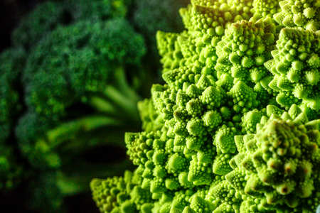 Macro photo green fresh vegetable ramonesco broccoli. Fresh green Romanesco Cauliflower on a black stone table.Vegetables for diet and healthy eating.Organic food.