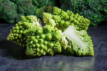 Macro photo green fresh vegetable ramonesco broccoli. Fresh green Romanesco Cauliflower on a black stone table.Vegetables for diet and healthy eating.Organic food. Reklamní fotografie - 132306000