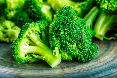 Macro photo green fresh vegetable broccoli. Fresh green broccoli on a black stone table.Broccoli vegetable is full of vitamin.Vegetables for diet and healthy eating.Organic food.