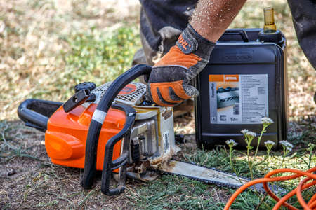 Ukraine Kiev June 22, 2019.Stihl chainsaw in Kiev. Professional technician working by repair service.Repairing chainsaw
