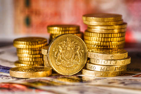 British Pound Coins against a background of British assorted bank notes,Business concept