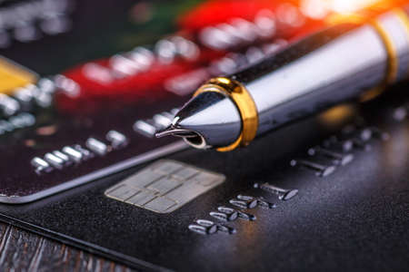 Credit card and ball pen,Online payment for purchases from online stores. Online shopping.Credit card close-up. Plastic card on black background 版權商用圖片