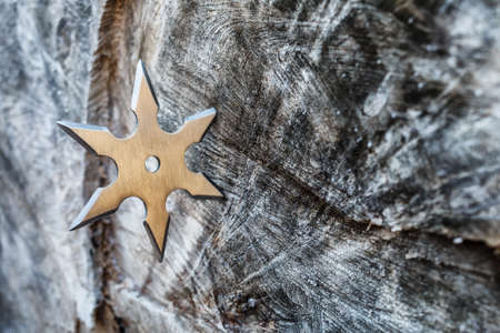 Shuriken (throwing star), traditional japanese ninja cold weapon stuck in wooden background,Silver shuriken with star shape.Samurai, throwing weapons