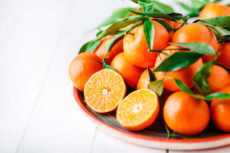 Tangerines (oranges, clementines, citrus fruits) with green leaves over wooden background with copy space.bowl of fresh mandarins