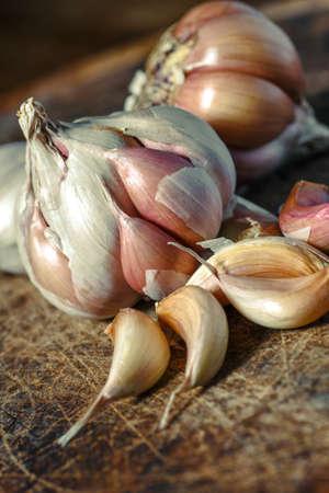 Bio-Knoblauch, Nahaufnahme Knoblauch auf Holzstruktur zum Kochen auf dunklem Hintergrund, Konzept gesunder Lebensstil. Frisch geschälte Knoblauchzehen und Zwiebeln.