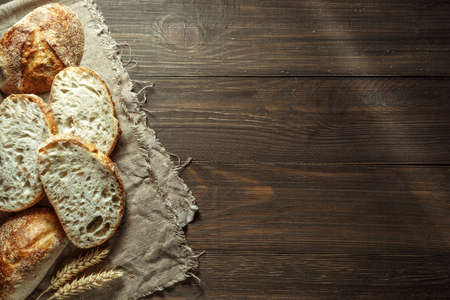 Bread, traditional sourdough bread cut into slices on a rustic wooden background. Concept of traditional leavened bread baking methods. Healthy food. Archivio Fotografico