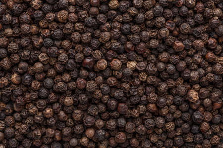 Peppercorn background. Dry black pepper seeds. Top view. Flat design. Macro spice background