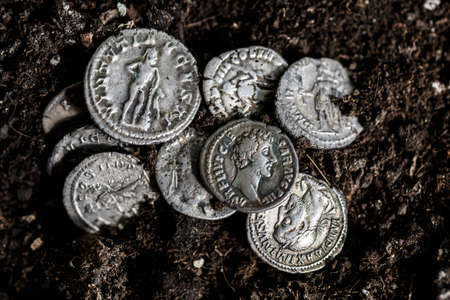 Ancient coin of the Roman Empire.Authentic silver denarius, antoninianus of ancient Rome.Roman silver coins covered in dirt.Antikvariat.