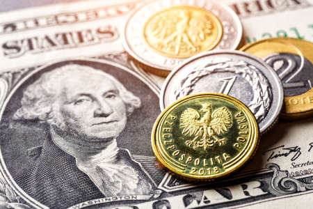 United States of America banknotes and Polish coins lie together, close-up of metal banknotes of Poland zloty together in paper banknotes of America.World economic crisis associated with coronovirus.