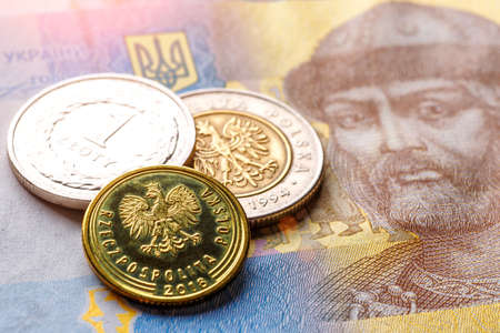 Ukrainian money - hryvnia banknotes and Polish coins lie together,  . Finance in Ukraine, of the hryvnia to the dollar exchange rate. World economic crisis associated with coronovirus.
