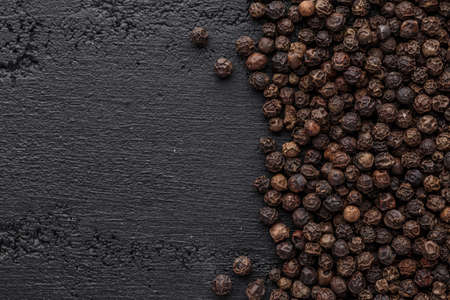 Peppercorn background. Dry black pepper seeds. Top view.On a black background. free space for your text.