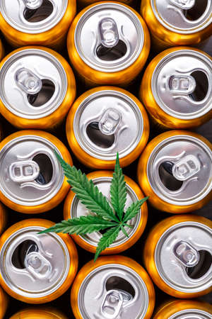 Golden beer cans.The sale of products and drinks with addition of hemp (cannabis) Beer cans with weed on one of them 스톡 콘텐츠 - 148969648