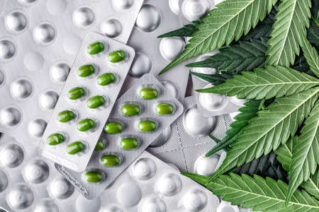 Marijuana leaf and medical pills.Legalizing marijuana for medical purposes.Hemp buds - medical marijuana concept.COVID 19 Coronavirus,