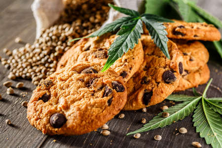 Cookies with cannabis and buds of marijuana on the table. A can of cannabis buds CBD Concept of cooking with cannabis herb. - Medical Legal Marijuana